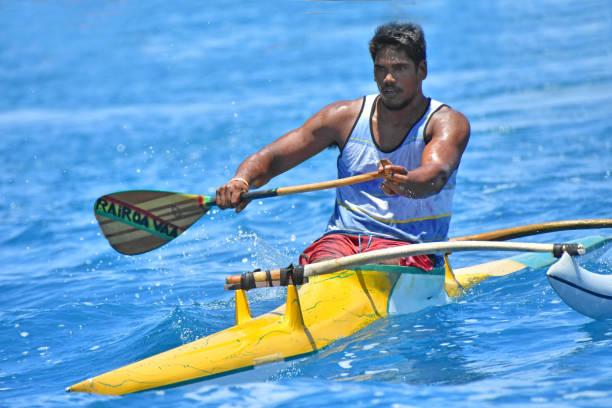 Polynesische Mann ein Ausleger-Kanu paddeln – Foto