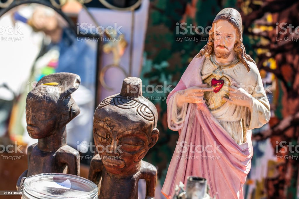 polytheism religion symbols, Christ and wooden African statues at garage sale stock photo