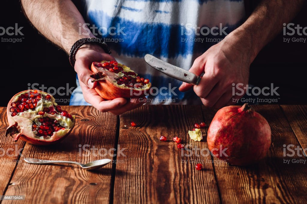 Pomegranate and Knife in Human Hands. stock photo