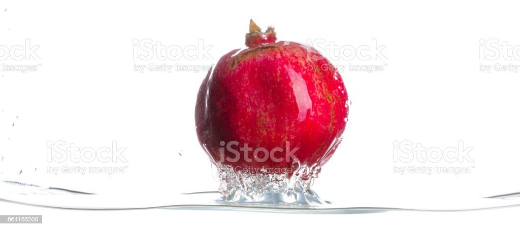 Pomegranate came from water. Drops of water. Isolated white background. Horizontal royalty-free stock photo