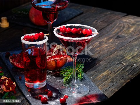 Pomegranate cranberry cocktail in various sugar rim drinking glasses. Low key