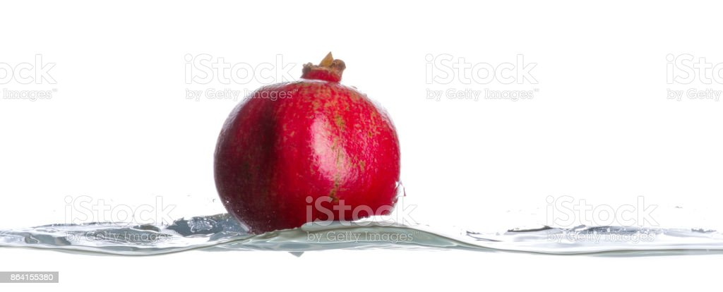 Pomegranate fall in to the turbulent water. Drops of water. Isolated white background royalty-free stock photo