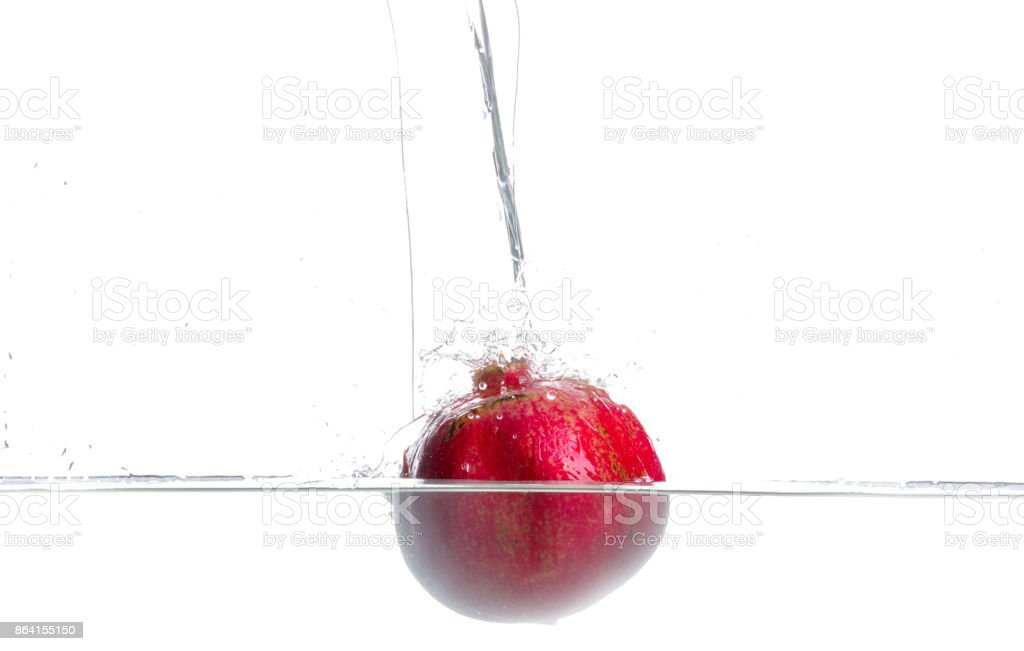 Pomegranate fall in to water. Drops of water. Isolated white background royalty-free stock photo