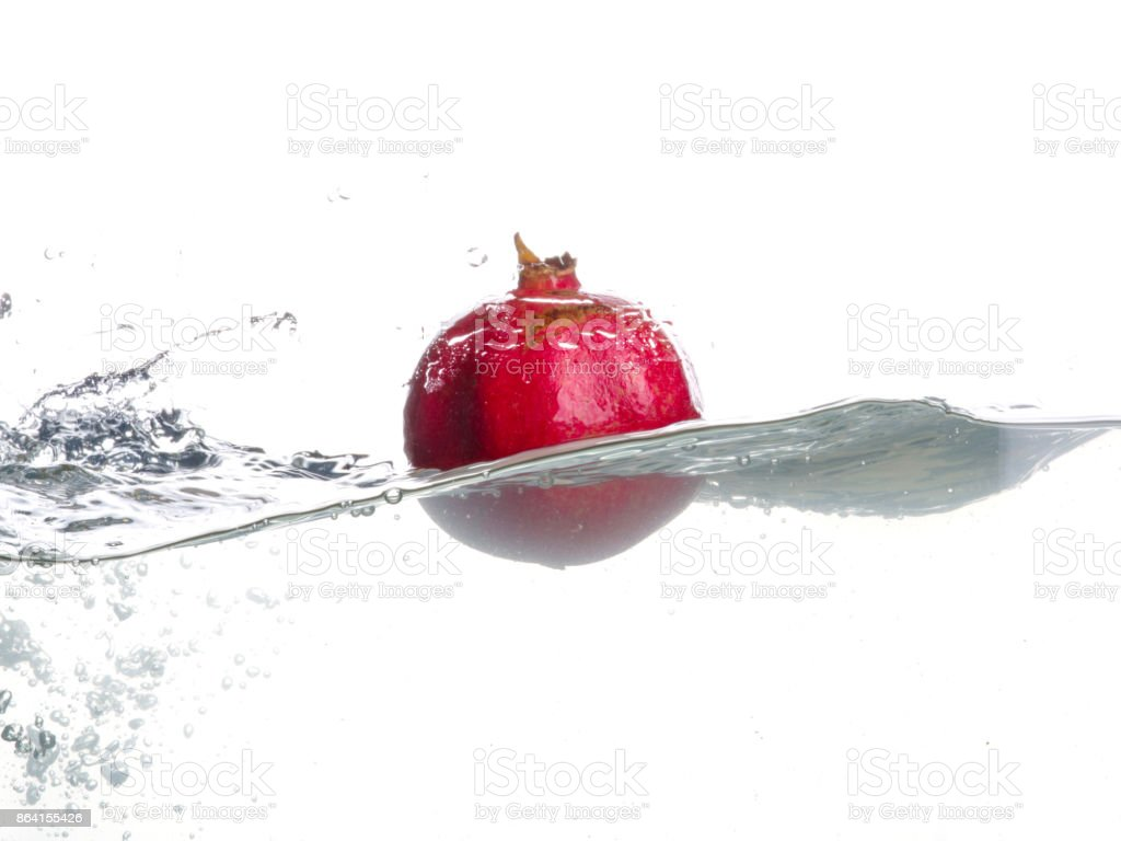 Pomegranate fall in water. Drops of water. Isolated garnet image on white background royalty-free stock photo