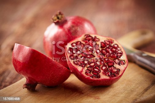 Sliced pomegranate on cutting board with knife and whole pomegranate behind.  Shot with shallow focus on sliced fruit.