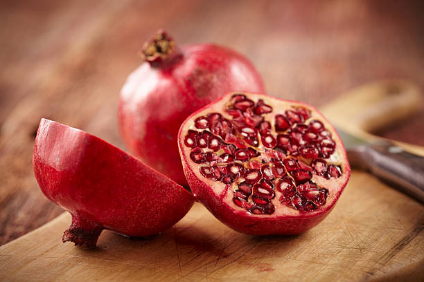 Pomegranate fruit on cut board stock photo