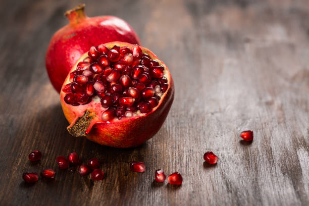 pomegranate fruit on wooden vintage background - romã imagens e fotografias de stock