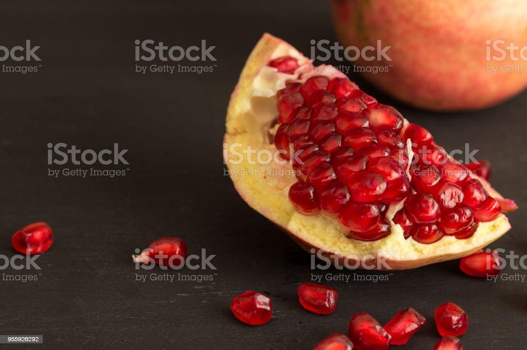 Pomegranate fruit slice and seeds still life on rustic black...
