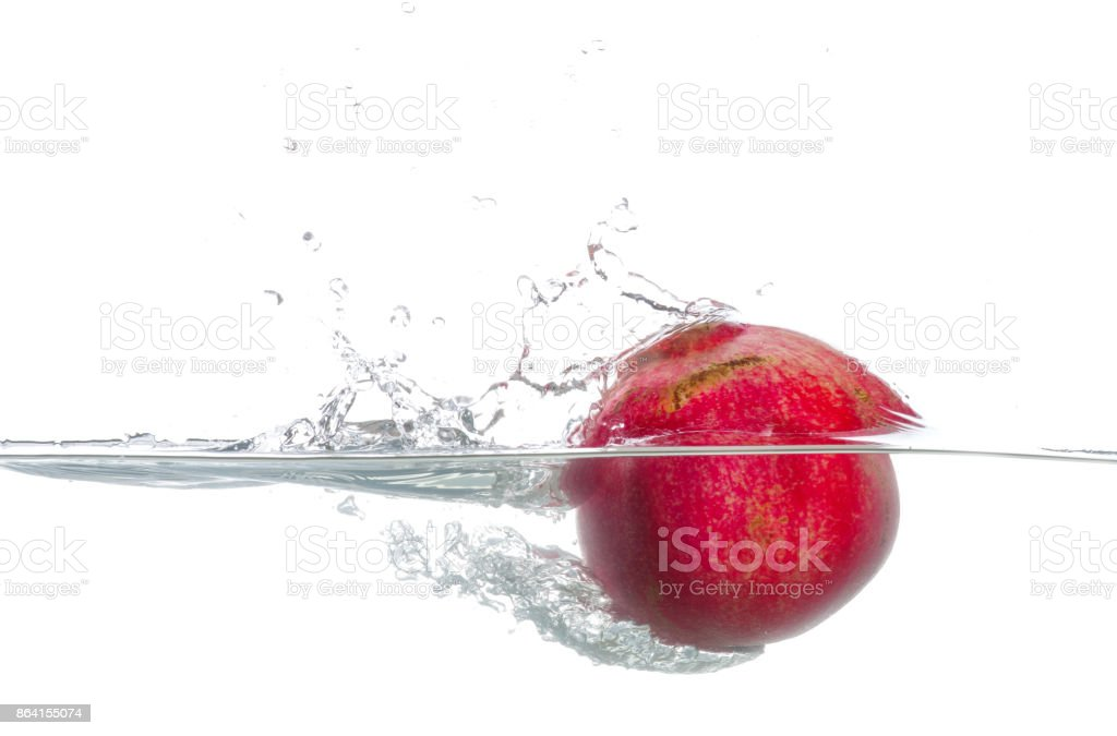 Pomegranate immersed in water. Drops of water. Isolated white background royalty-free stock photo