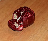 A pomegranate ripe with bright red seeds with one side peeled on a wooden surface.
