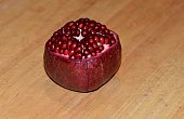 A pomegranate ripe with bright red seeds with top peeled,  on a wooden surface.
