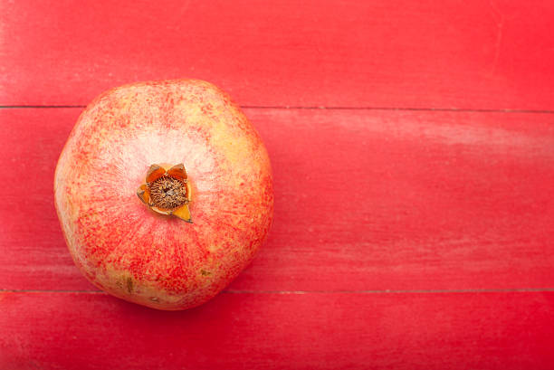 Pomegranate on a red wooden background stock photo