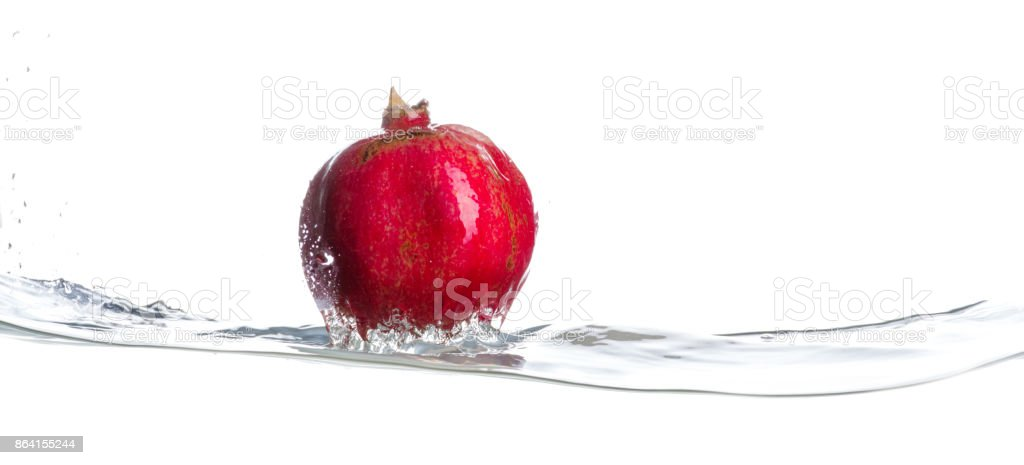 Pomegranate on water surface. Drops of water. Isolated white background stock photo