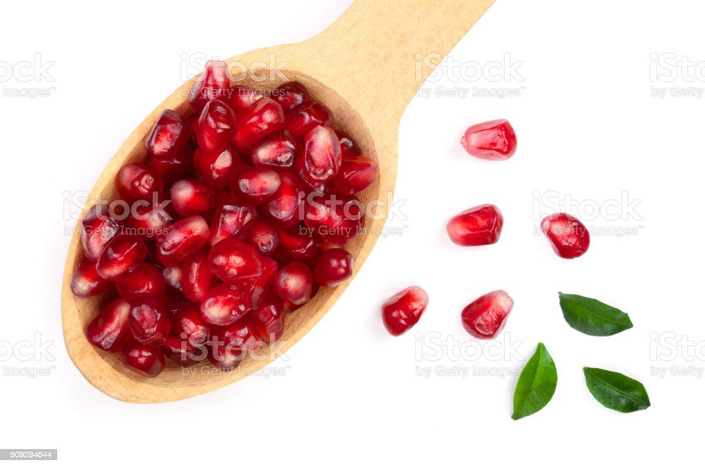 pomegranate seeds in wooden spoon with leaves isolated on white background. Top view. Flat lay pattern stock photo