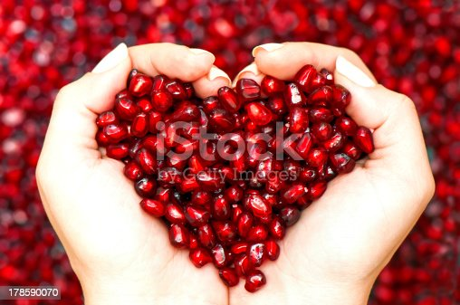 istock Pomegranate seeds shaping heart in hands 178590070