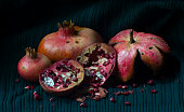 close-up of pomegranate whole and open-face with seeds in light painting picture