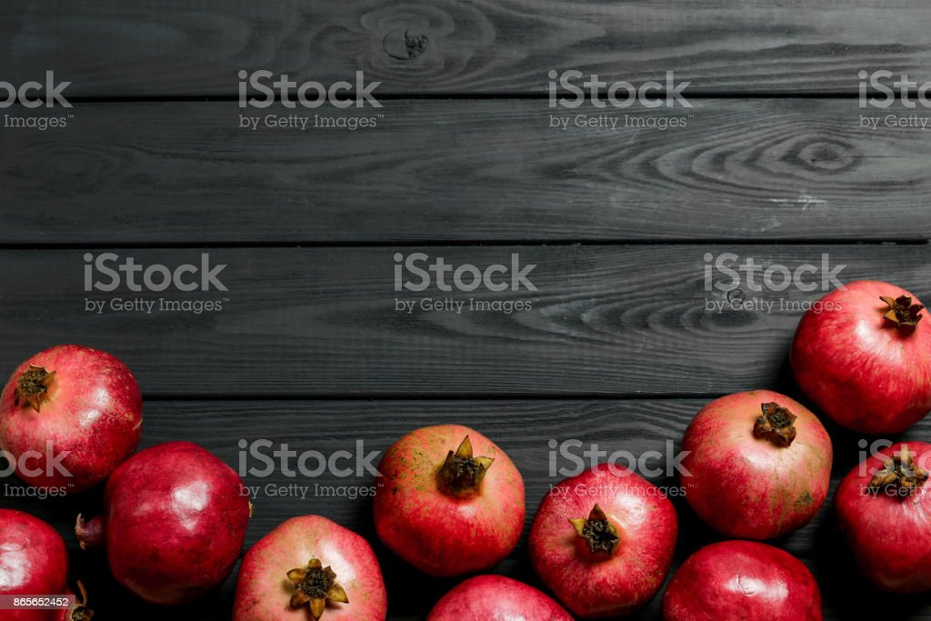 Pomegranates on black wooden background Top view with a copy space stock photo