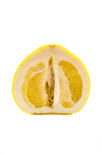 Half of ripe yellow pear-shaped pomelo fruit isolated on white background. Pomelo fruit is cut vertically.