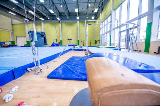 pommel horse and other gymnastics equipment in empty gym - uneven parallel bars stock photos and pictures