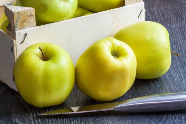 pommes golden devant un cageot sur fond noir - golden photos et images de collection