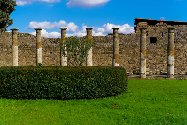 Pompeii, Italy House of the Vettii archaeological remains. Day view of ancient ruins at the courtyard with columns by a stone structure. Remains after Mount Vesuvius volcanic eruption in 79 AD. stock photo