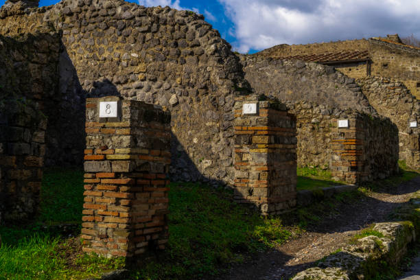 Pompeii, Italy Roman architecture city block remains with numbered homes entrances. Numbers in doorways identifying stone houses ruins, insula, after Mount Vesuvius volcanic eruption in 79 AD. stock photo
