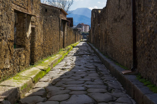 Pompeii, Italy secondary narrow street along remaining houses. Day view of structured formation of cobblestoned path to accommodate traffic inside the town. stock photo