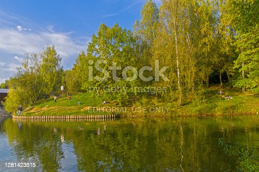 Moscow, Russia - September 24, 2020: People are relaxing on the banks of the pond on a warm September evening. Teplostanovsky forest park, Moscow.