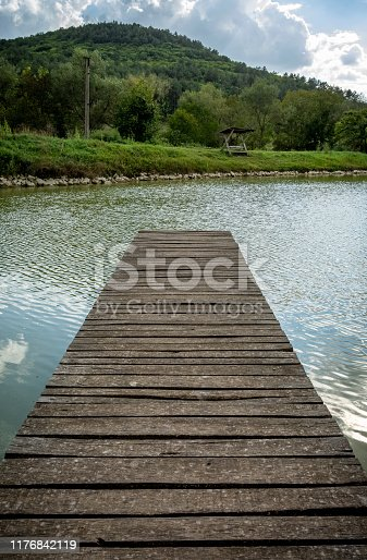 pier on a calm pond in a middle of a forest,