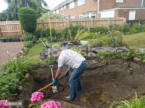 A senior man reconstructing a pond from a figure of eight to a rectangular shape using pick axe and spade.