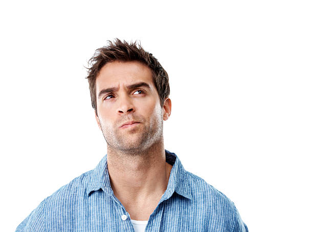 Pondering a possible solution Handsome young man looking thoughtful while isolated on white - copyspace raised eyebrows stock pictures, royalty-free photos & images