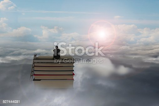 istock pondering businessman sitting on stack of books with sunlight cl 527444031