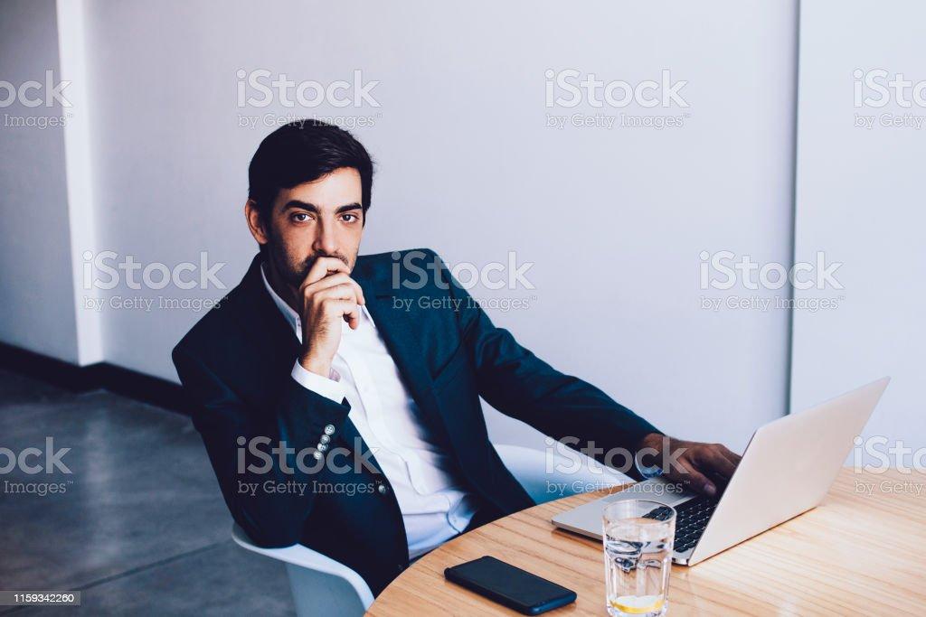 Pondering Businessman Spending Time In Workspace Using