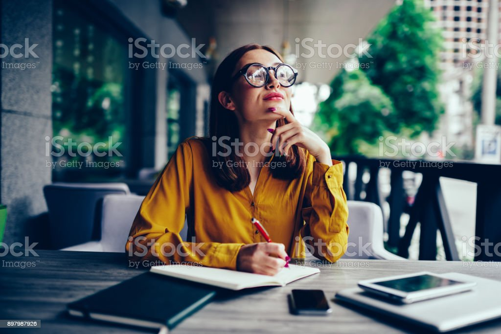 Pondering cute talented student in cool spectacles looking away and thinking while preparing for upcoming exams.Pensive charming redhead hipster girl writing down information to notepad in cafe stock photo