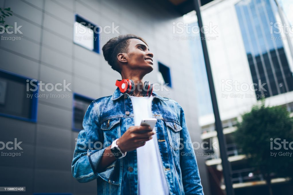 Pondering hindu student with headphone on neck looking away while...