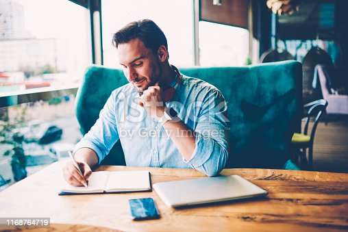 1174436608 istock photo Pondering male entrepreneur with headphones on neck writing down organization plan of productive work for own startup project in notepad spending time indoors in stylish coffee shop 1168764719