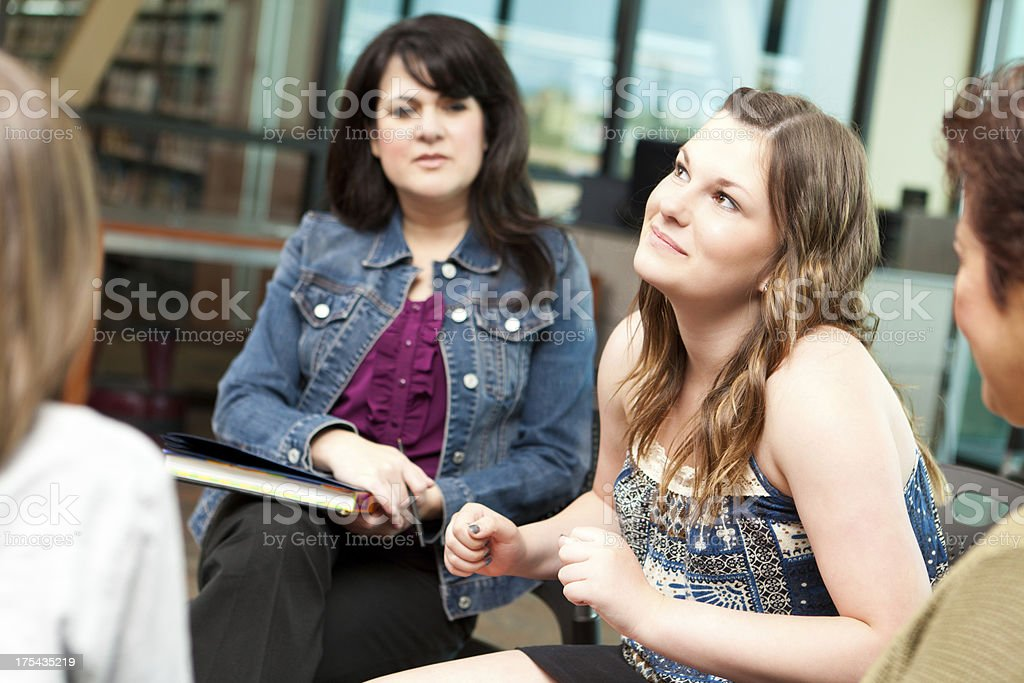 Pondering teenager in a group discussion setting royalty-free stock photo