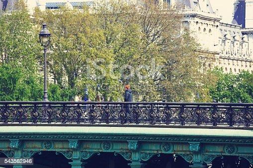 Paris, France - April 27, 2016: People are crossing the bridge; Hotel de Ville in the background.