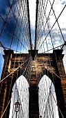 Vue en contre-plongée d'une tour et des cordages d'acier du pont de Brooklyn à New York.