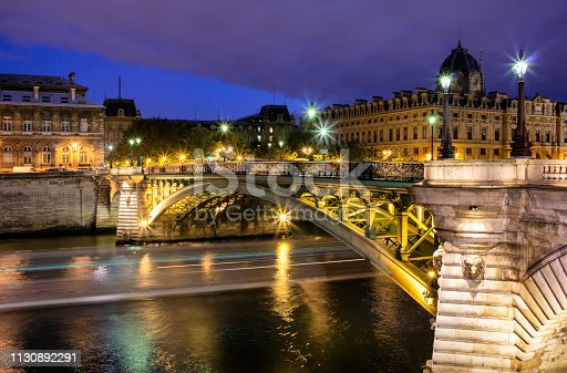 A boat passes beneath the Pont Notre-Dame in Paris at night.