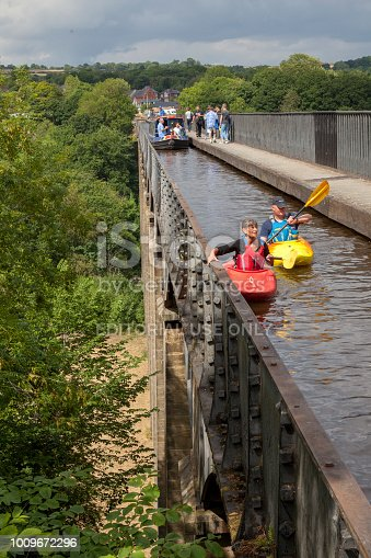 The Pontcysyllte Aqueduct carries the Llangollen Canal across the River Dee in north east Wales.  This view is from the top of the aqueduct. People can be seen walking on the towpath and a canalboat can be seen on the water with canoes paddling also on the water