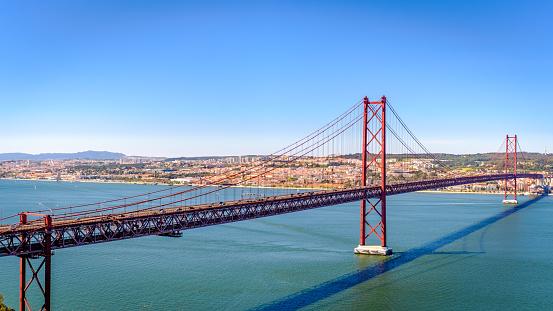 Ponte 25 de Abril. Most famous bridge in Portugal. Lisbon. Red bridge. Sunny day.