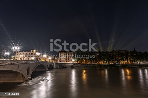 Ponte della Vittoria Bridge over the River Adige in Verona, Italy at night. Lights from street lights and even more lights from an outdoor concert in the background.