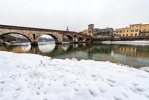 Verona, the ancient Ponte Pietra (Stone bridge, 1st century B.C.) and the River Adige in winter with snow. UNESCO world heritage site, Veneto, Italy, Europe