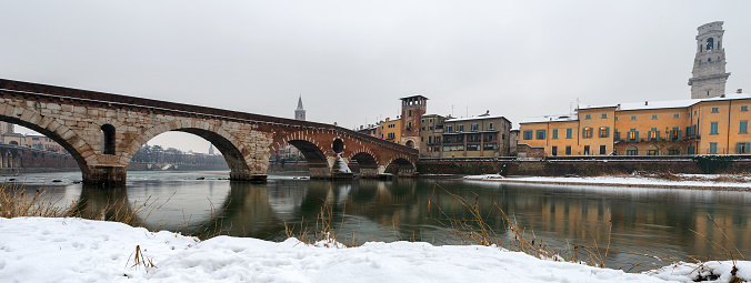 Verona, Ponte Pietra (Stone bridge) - 1st century B.C., and Adige river in winter with snow. Veneto, Italy, Europe