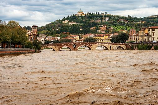 Verona, Ponte Pietra (Stone bridge), I century B.C, and Adige river in flood after several violent storms. UNESCO world heritage site, Veneto, Italy, Europe.