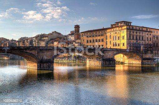 The Ponte Santa Trinita bridge across the river Arno and historical houses in Florence, Italy