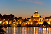 Tiber river and Ponte Sant'Angelo bridge at dusk, St. Peter's Basilica in Vatican city is seen in the background, Italy.