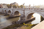 Ponte Sant'Angelo in Rome at sunset with tourists, on the Tiber river