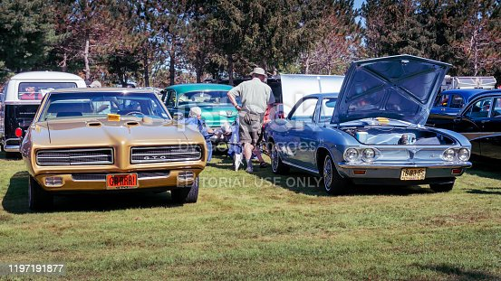 Hilden, Nova Scotia, Canada - September 21, 2019 :  A pair of classic General Motors cars, 1969 Pontiac GTO & 1966 Chevrolet Corvair at Scotia Pine Show & Shine at Scotia Pine Campground. A man stands near the rear of the Corvair with hand on rear fender.